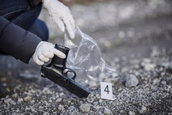 Crime scene investigation - collecting pistol on forest way