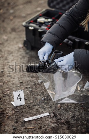 Crime scene investigation - collecting pistol on the ground - Shutterstock ID 515030029
