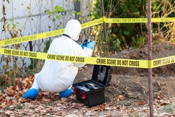 Crime scene investigation. Forensic science specialist photographing human remains.