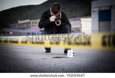 Crime scene, murder, investigation, bloody trail on asphalt, ongoing investigation, camera expert evidence of murder