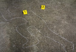 Crime scene. Shape of body on concrete texture. Bullet shell next to
