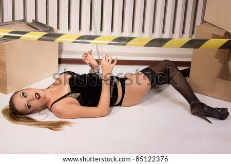 Crime scene simulation: dead blonde in the handcuffs lying on the floor