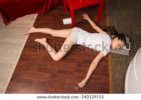 Crime scene simulation: overdosed victim lying on the floor - stock photo