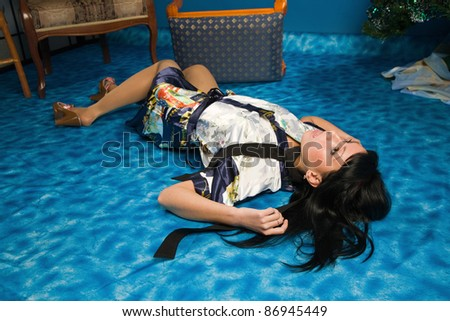 Crime scene simulation: strangled  brunette lying on the floor