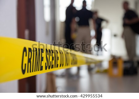 Photo of  crime scene tape in building with blurred forensic team background