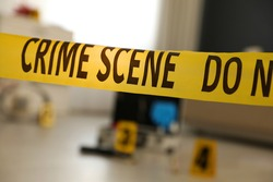 Crime scene with evidences and criminologist case, focus on yellow tape