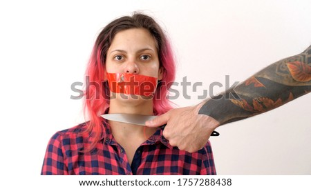 Criminal brings the knife to the victim's throat with tape on mouth. Portrait of a frightened woman with pink hair. Self-isolation domestic violence. Prohibition of freedom of speech. Stock photo ©