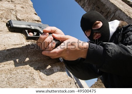 Criminal in black mask aiming his target with a pistol