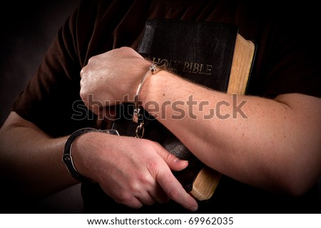 Criminal in handcuffs clutches his bible in prison ministry setting.
