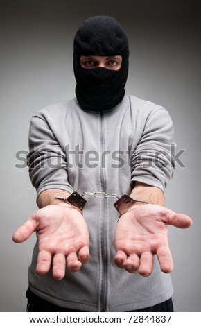 Criminal locked in handcuffs asking for freedom - stock photo