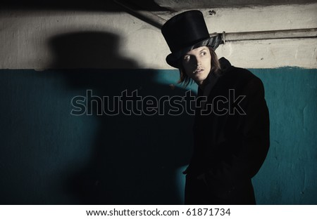 Criminal man in vintage black coat and top hat in the dark interior. Natural darkness and colors