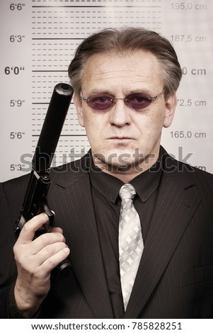 Criminal man portraited with silenced pistol in front of mug board #785828251