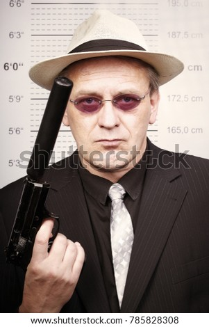 Criminal man portraited with silenced pistol in front of mug board #785828308