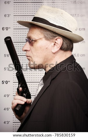 Criminal man portraited with silenced pistol in front of mug board #785830159