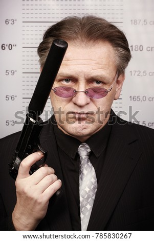 Criminal man portraited with silenced pistol in front of mug board #785830267