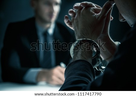 Criminal man with handcuffs in interrogation room feeling guilty after committed a crime Stock photo ©