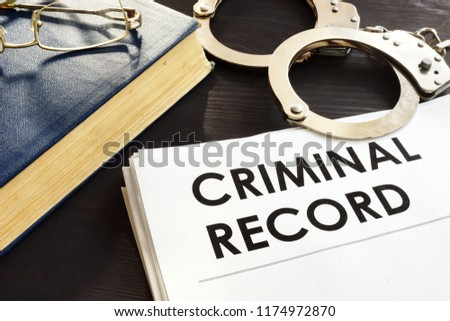 Criminal record and handcuffs on a desk. #1174972870
