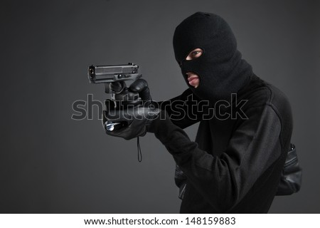 Criminal. Side view of men in black balaclava aiming with a gun and flashlight while standing isolated on black