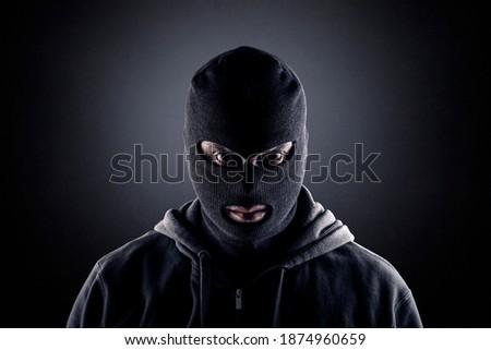 Criminal wearing black balaclava and hoodie in the dark Stock photo ©