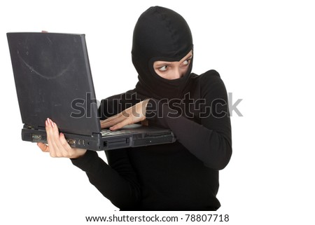 criminal woman in dark clothes and balaclava with the laptop