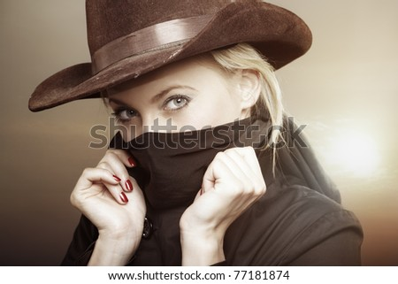 Criminal woman with cowboy hat during hot sunset. Creative colors added for movie effect - stock photo