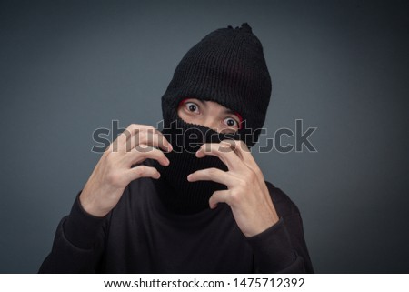Criminals wear a mask in black on a gray background. #1475712392