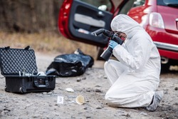 Criminological expert collecting evidence at the crime scene. Law and police concept