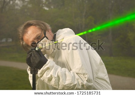 Photo of  Criminologist technician in protective suit and mask working with ballistics laser