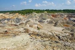 Crimson, acidic lakes amid colorful, lifeless mud hills and blue, cloudy skies. Open pit mining. A green forest in the background. The industrial landscape is similar to the Martian landscape.