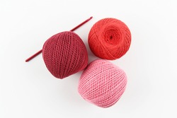 Crimson, red and pink cotton thread balls and crochet hook on white background. The concept of a favorite hobby of needlework, needlework and needlework. Top view. Flatley. Copyspace.