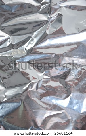 Crinkled tinfoil as a background with black grey and silver colors