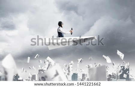 Crisis management and control in difficult situation concept. Businessman in aviator hat driving paper plane in storm. Pilot flying in small airplane. Megalopolis panorama with dramatic sky. #1441221662