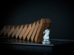 Crisis management, risk management, crisis solving or problem solving concept. Knight chess stopping wooden dominoes from collapsing on chessboard in black scene.