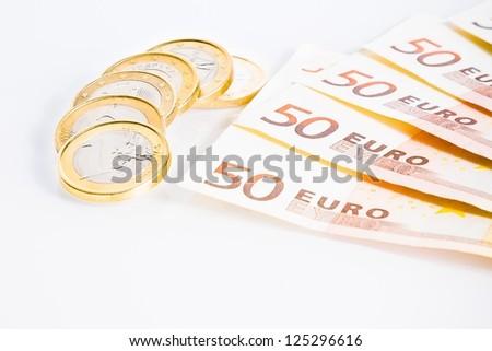 crisis of eurozone, detail of some euro coins on 50-euro banknotes on white background