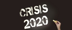 Crisis 2020 text on a chalk board. An economic and financial crisis is coming due to the prevailing coronavirus around the world.