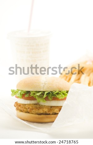 crisp chicken burger with tomato onion cheese lettuce isolated