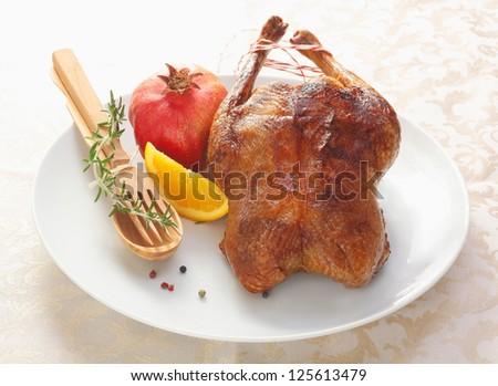 Crisp golden roast chicken with fresh rosemary, a slice of orange and a whole pomegranate on a plate with wooden serving utensils