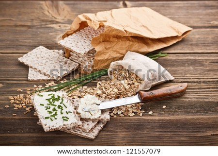 Crispbread with fresh cream cheese on wooden background