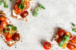 Crispbreads with feta, colorful cherry tomatoes, onions, and herbs. Toast with cream cheese and tomatoes on a gray background top view. Free space for text. Tasty breakfast or snack. Food background