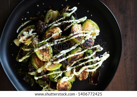 crispy baked brussel sprouts drizzled with sauces on a black plate on dark wooden table