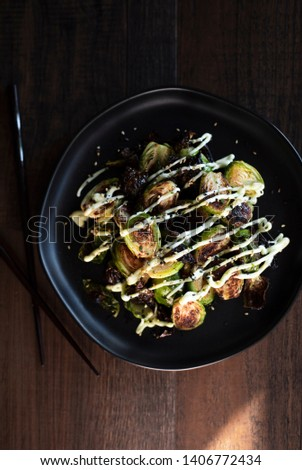 crispy baked brussel sprouts drizzled with sauces on a black plate on dark wooden table with chopsticks