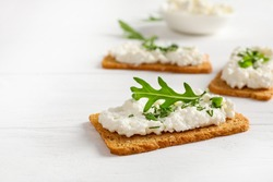 Crispy bread crackers with cottage cheese and green herb on white background. Copy space.