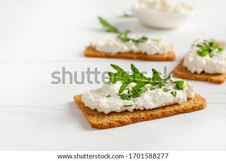 Crispy bread crackers with cottage cheese and green herb on white background. Copy space. Foto stock ©