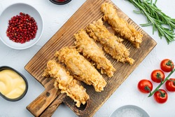 Crispy chicken tenders cuts on white background, top view.