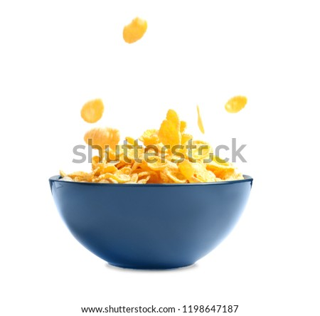Crispy cornflakes falling into bowl on white background #1198647187