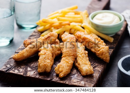 Crispy Fish and Chips with Tartar Sauce Traditional British food on a wooden board #347484128