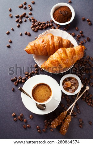 Crispy fresh croissants and cup of coffee on a black background, morning breakfast, selective focus