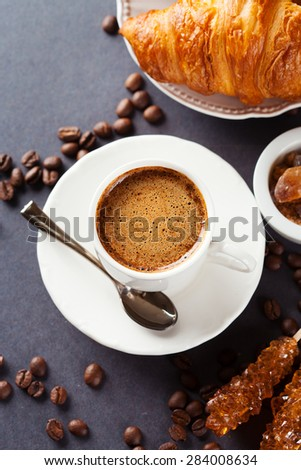 Crispy fresh croissants and cup of coffee on a black background, morning breakfast, top view