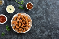 Crispy fried breaded chicken bites in white bowl over blue stone background with copy space. Tasty chicken nuggets. Top view, flat lay