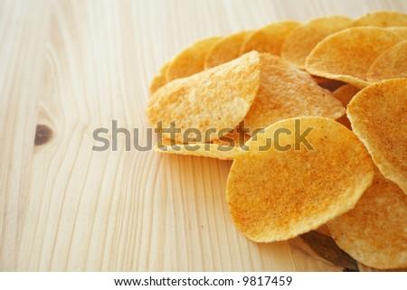 Crispy golden brown potato chips on a wooden presentation plate (shallow depth of field)